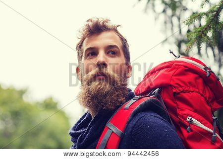 adventure, travel, tourism, hike and people concept - man with beard and red backpack hiking poster