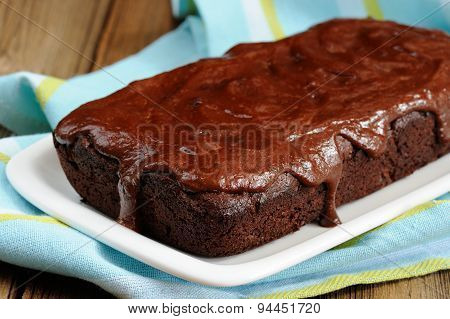 Dark Chocolate Cake With Leaky Chocolate Icing In White Plate