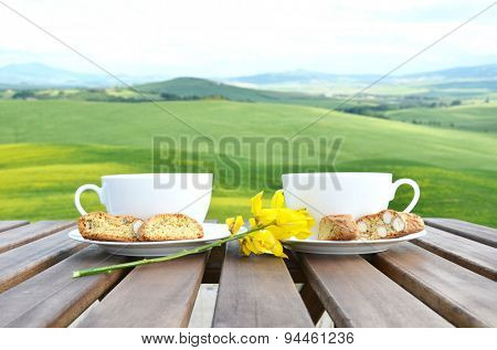 Coffee and cantuccini on the wooden table against Tuscan landscape. Italy poster