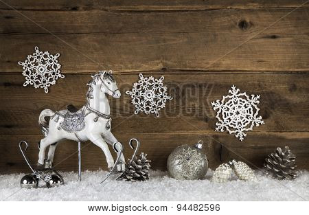 Old wooden horse on a background with snow. Nostalgic christmas decoration in vintage style.