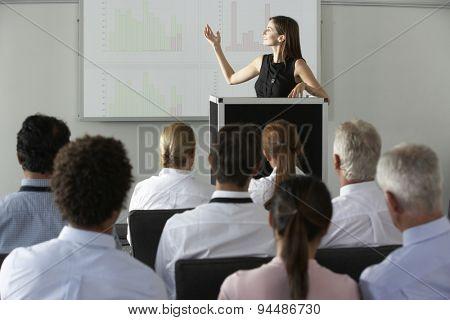 Businesswoman Delivering Presentation At Conference poster