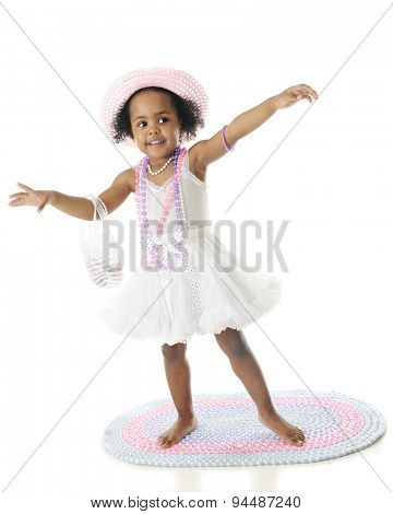 A beautiful two year old African American all gussied up in her petticoat, pearls, hat and purse.  She's barefoot and standing on a rag rug.