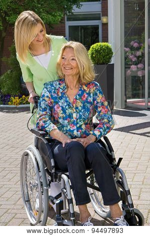 Nurse With Senior Woman In Wheelchair Outdoors