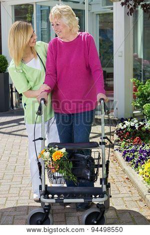 Nurse Helping Senior Woman To Walk With Walker