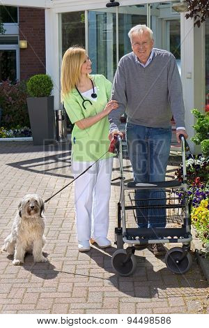 Nurse Helping Man With Walker Take Dog For Walk