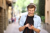 Happy guy walking and using a smart phone to listen music with headphones poster