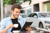 Happy man reading an ebook or tablet in a coffee shop terrace holding a cup of tea poster