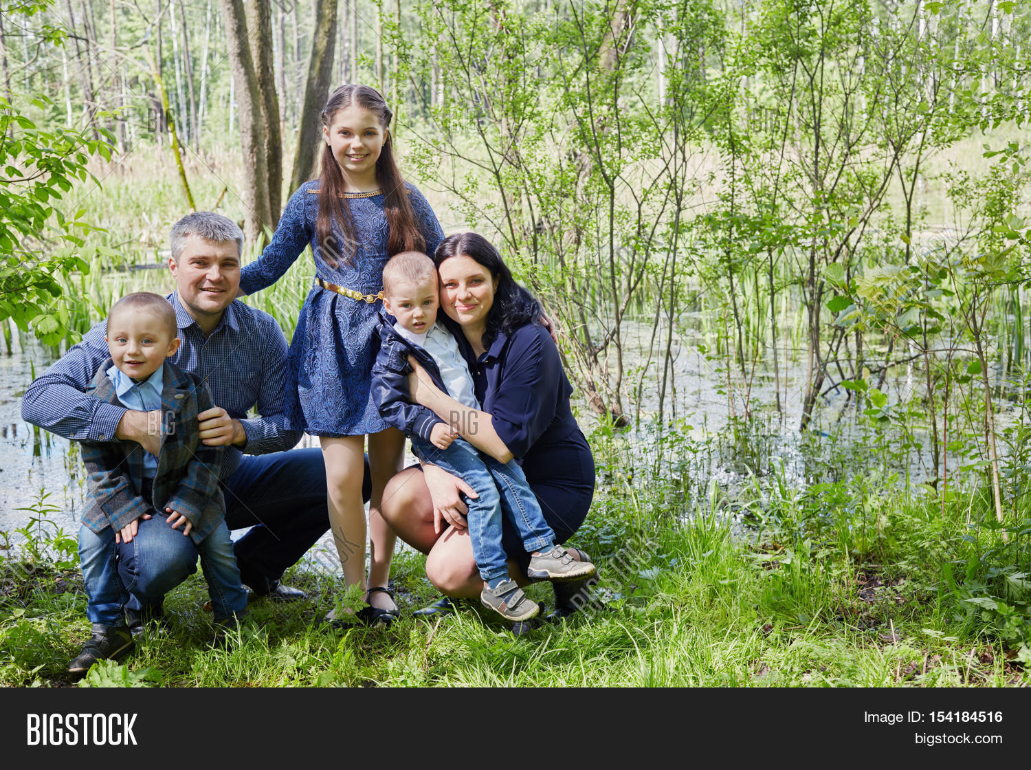 Family Of Five Poses On Boggy Pond Shore In Summer Park