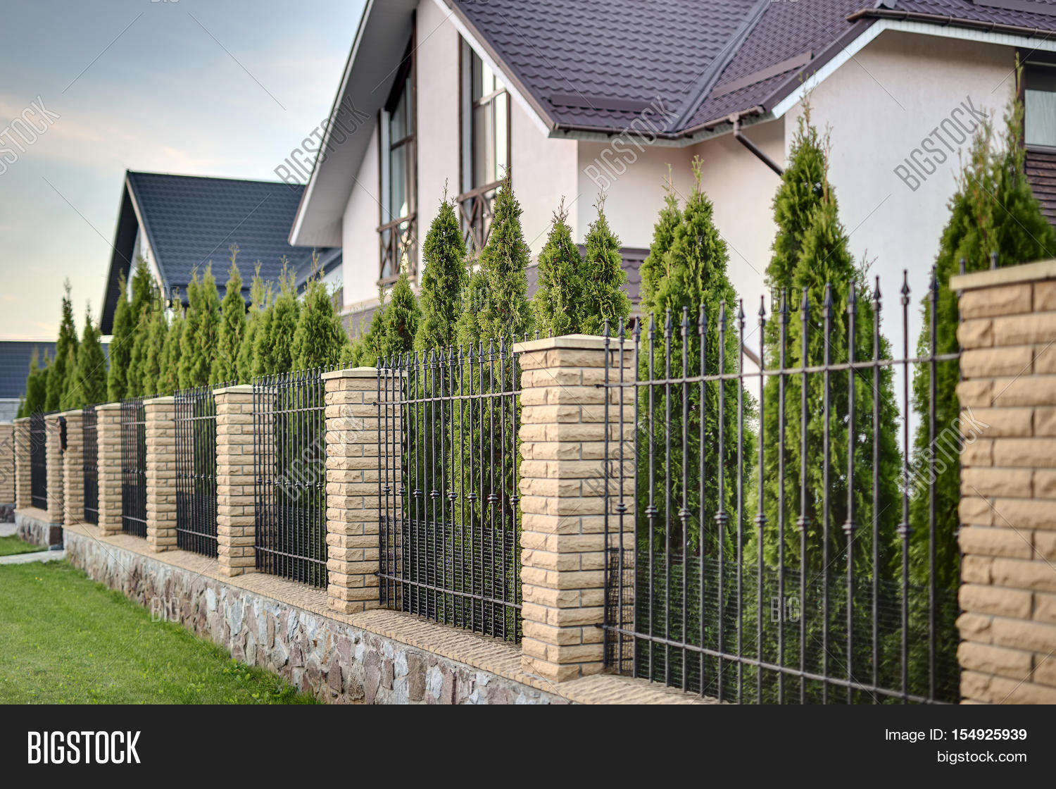 Metal Fence With Brick Columns On The Background Of Line Green Trees And Country
