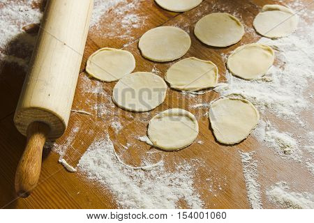 Circles of dough and rolling pin on the wooden table. Homemade process of preparation Russian Belarussian Ukrainian meals