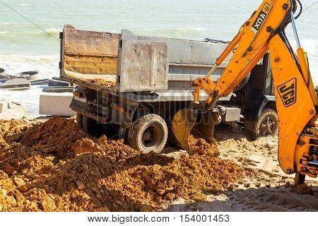 Odessa, Ukraine -17 October 2016: Excavator Digs Sand On A Sea Beach. Wheel Loader Excavator Doing E