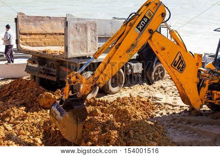 Odessa, Ukraine -17 October 2016: Excavator Digs Sand On A Sea Beach. Wheel Loader Excavator Doing E
