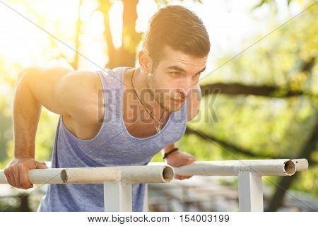 Fitness young man training on parallel crossbars. Image with lens flare effect