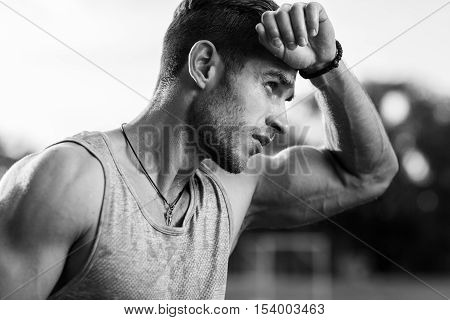 Black-and-white portrait of tired muscular male wiping sweat of forehead after training
