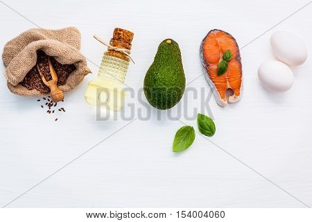 Selection food sources of omega 3 . Super food high omega 3 and unsaturated fats for healthy food. Extra virgin olive oils salmon fillet flax seeds white eggs and avocado on white wooden table.