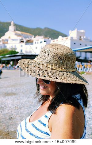 Portrait of adult beautiful woman in sunglasses and straw hat wearing striped top and denim skirt walking on seafront