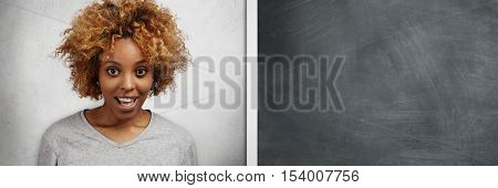 African Student Girl With Afro Haircut And Ring In Her Nose Standing At Blank Copy Space Blackboard,