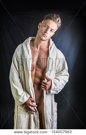 Handsome totally naked young man wearing white bathrobe, on dark background