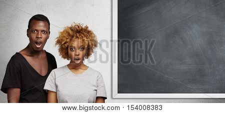 African Man And Woman Standing Close To Each Other At Blank Chalkboard With Copy Space For Your Text