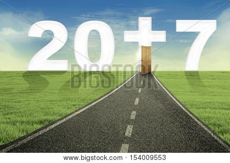 Concept of Happy New Year 2017. Portrait of empty road toward number 2017 with a cross symbol shaped a doorway