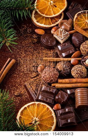 Christmas sweets: assortment of chocolates, truffles, candies, chocolate barks, spices and nuts. Christmas spirit still life