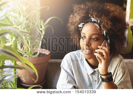 Indoor Shot Of Happy Young Dark-skinned Woman Using Mobile Phone While Talking To Friends, Sitting A