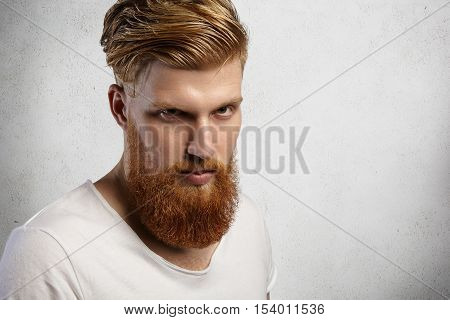Close Up Portrait Of Serious Attractive Young European Man With Long Fuzzy Beard, Looking At Camera