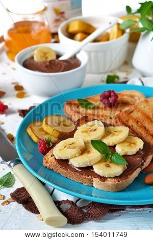 Good morning - toast with Nutella banana and honey. White food background.
