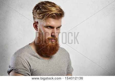 Portrait Of Courageous Model With Long Fuzzy Beard And Trendy Haircut Posing Indoors. Studio Shot Of