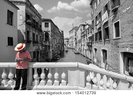 Black and white bridge over a canal in Venice, with selective red color on the striped shirt of a gondolier