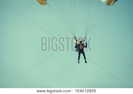 Skydiver On colorful Parachute In Sunny Blue Sky