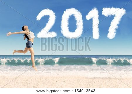 Image of young woman enjoying her holiday while dancing on the beach with clouds shaped number 2017 on the sky