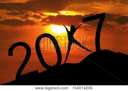 Silhouette young woman jumping on the hill and 2017 years while celebrating new year 2017