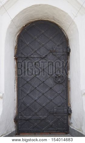 The wooden door of the orthodox church of the seventeenth century. The door latches and reinforced with iron bars