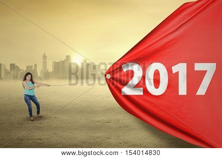 Young casual woman pulling a banner with number 2017 isolated over bokeh background