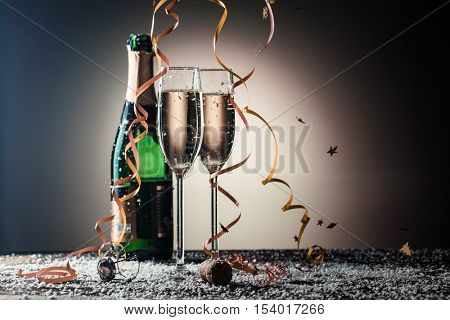 Bottle of champagne, wineglasses with golden ribbons, snowflakes and serpentine
