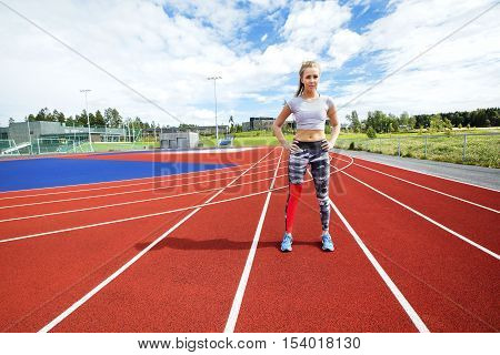 Full length of sporty young woman standing with hands on hips on running tracks
