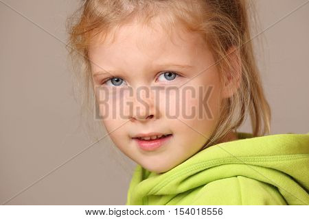 Portrait of a serious looking child girl on gray background