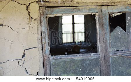 Rickety old wooden window frame with broken window pane. Part of old mud hut facade covered with a cracks.
