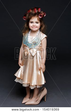 Cute little girl in dress and big high heels shoes with red lips and rollers in hair standing over dark background. Studio shot. Copy space.