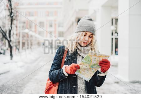 Young blond curly female tourist in warm clothes and red gloves with London map looking for a way in winter city blurred white background