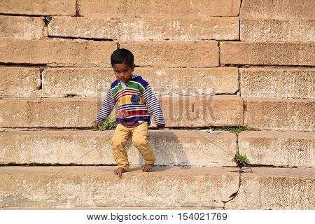 VARANASI, UTTAR PRADESH, INDIA - FEBRUARY 17, 2016 - Indian baby going down the steps of the ghats