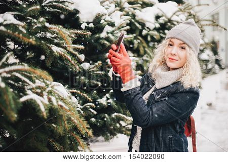 Young blond curly female tourist in warm clothes and red gloves making photo of spruce or selfie on a smartphone