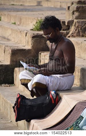 VARANASI, UTTAR PRADESH, INDIA - FEBRUARY 17, 2016 - Unidentified indian man with glasses reading on the ghats