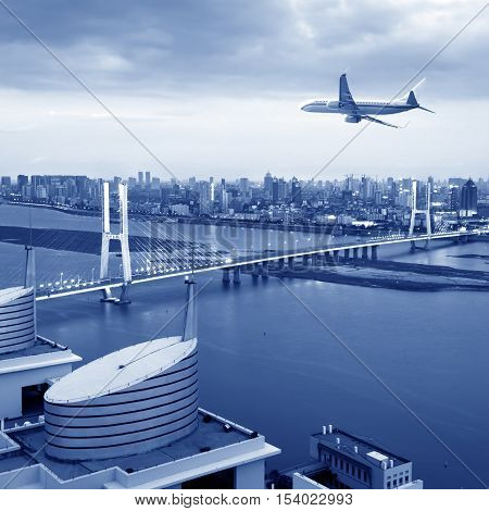 The plane flew over the city's modern bridge.