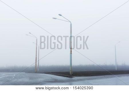 Street lights, foggy misty, lamp post lanterns, deserted road in mist fog, wet asphalt tarmac.