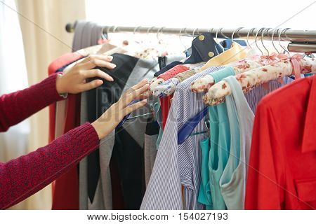 Female hands rummaging in clothes in shop