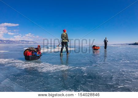 A Woman And A Man With A Sledge And Trekking Pole Is Ice Of Baikal