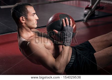Intense workout. Young brawny man doing some abdominal crunches on floor with help of special fitness ball.