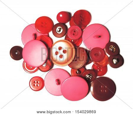 Red and pink sewing buttons, heap of buttons. Isolated on white background.